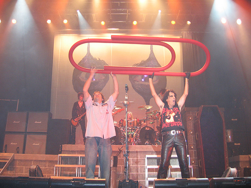 Alice Cooper holds up a massive red paperclip